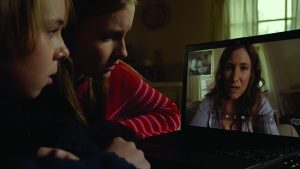 Becca (Olivia DeJonge) and Tyler (Ed Oxenbould) sky ping with Mom (Kathryn Hahn) in The Visi