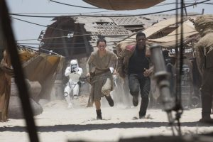 Rey (Daisy Ridley) and Finn (John Boyega) run for it in Star Wars: The Force Awakens